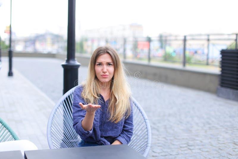 Persona femenina contrariedad que se sienta en el café de la calle y que hace caras fotos de archivo