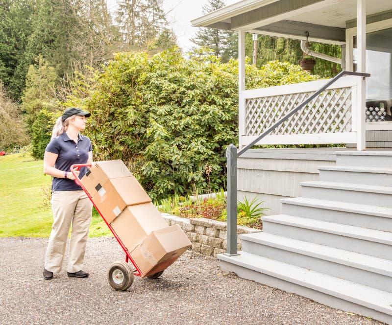 Persona femenina de la entrega con el camión y las cajas de mano imagen de archivo