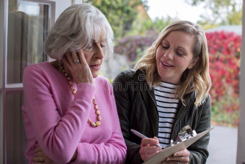 Persona femenina de las ventas que intenta persuadir a la mujer mayor de comprar fotos de archivo libres de regalías