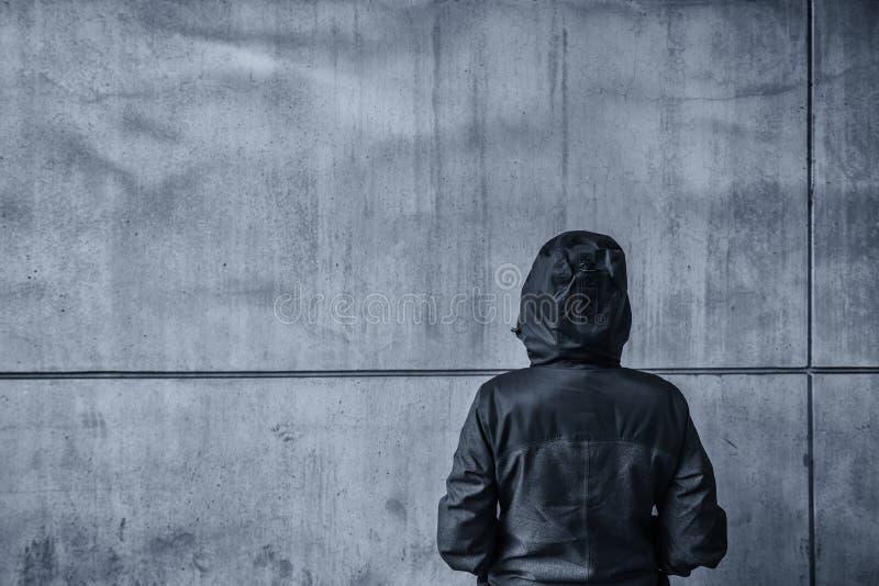 Persona femenina encapuchada irreconocible que hace frente al muro de cemento como insu imágenes de archivo libres de regalías