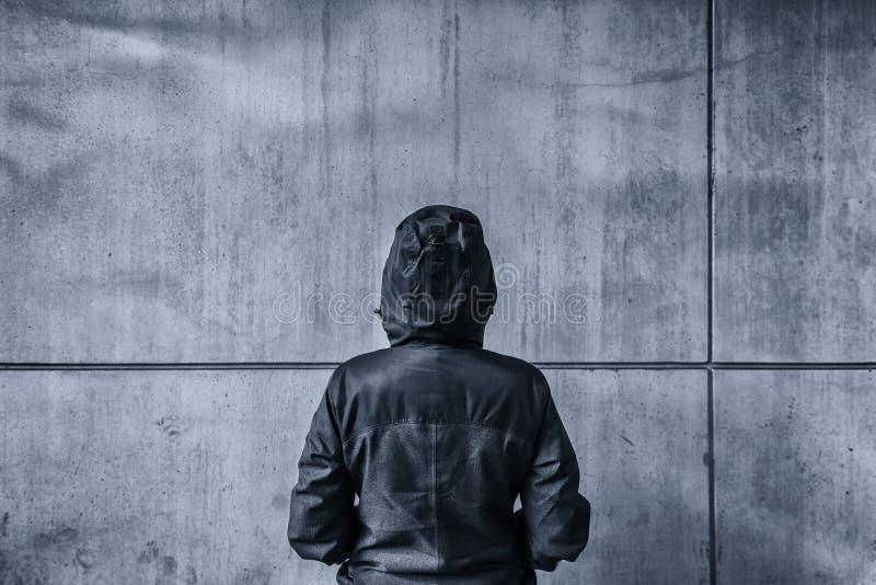 Persona femenina encapuchada irreconocible que hace frente al muro de cemento como insu imagen de archivo libre de regalías