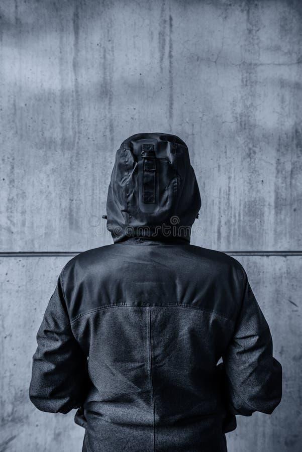 Persona femenina encapuchada irreconocible que hace frente al muro de cemento como insu fotografía de archivo
