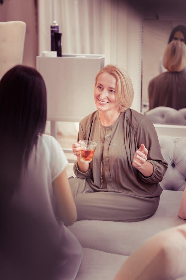 Persona femenina mayor contenta que se sienta en el sof imagenes de archivo