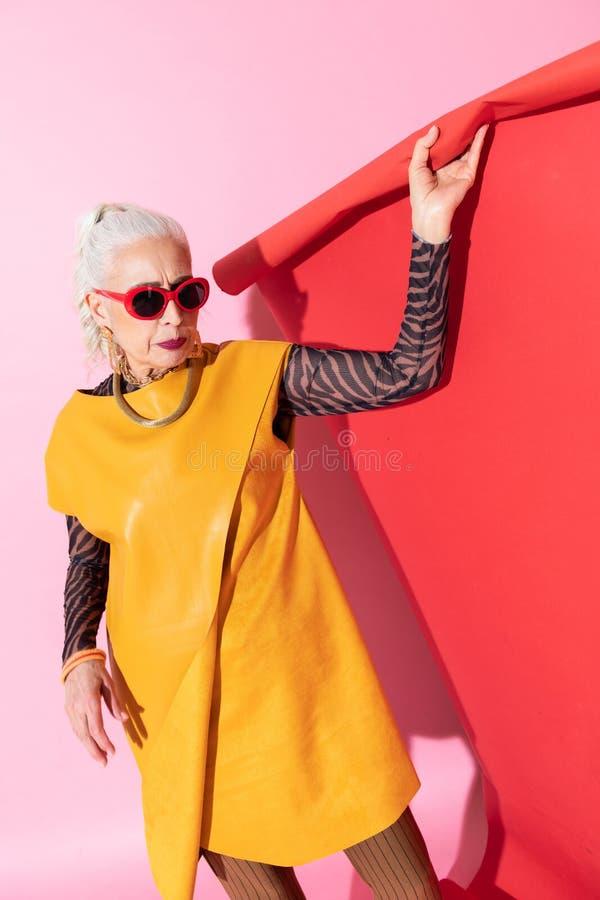 Persona femenina mayor seria que se prepara para tirar foto de archivo
