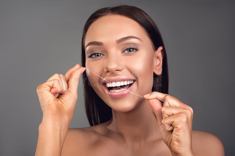 Persona femminile allegra che usando filo per i denti immagini stock libere da diritti