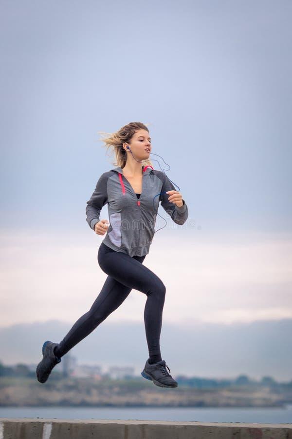 Persona femminile che corre lungo il lungomare nel giorno nuvoloso fotografia stock