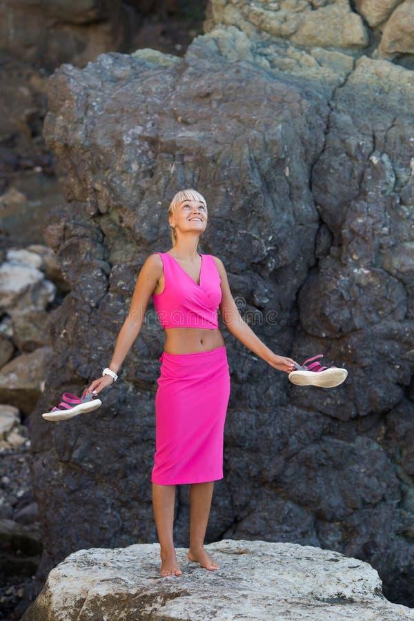 Persona femminile dai capelli bionda abbronzata che riposa al posto isolato della spiaggia rocciosa selvaggia fotografia stock
