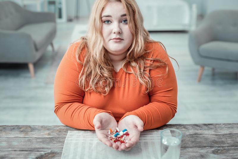 Persona femminile di peso eccessivo incantante che dimostra le sue pillole immagine stock libera da diritti