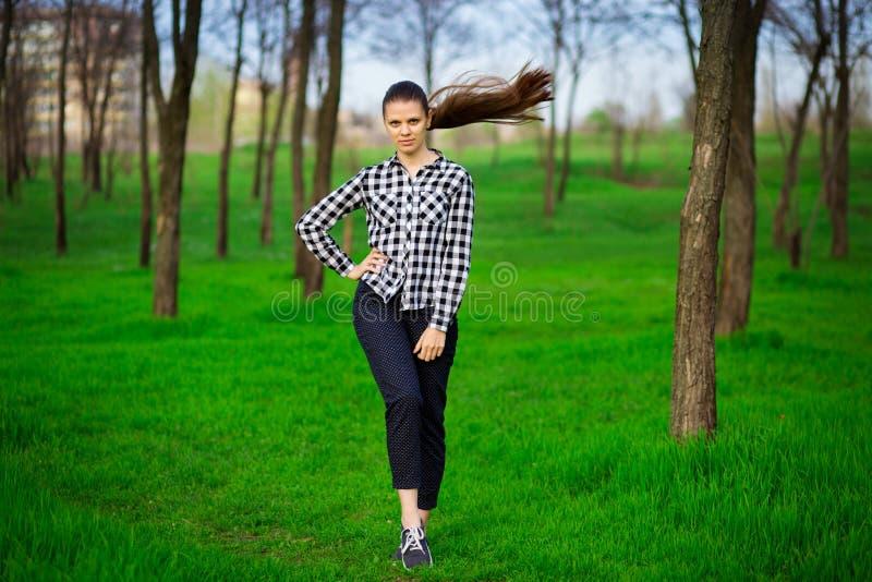 Persona femminile graziosa che riposa nel parco su erba verde Concetto di bellezza e di tempo libero fotografia stock libera da diritti