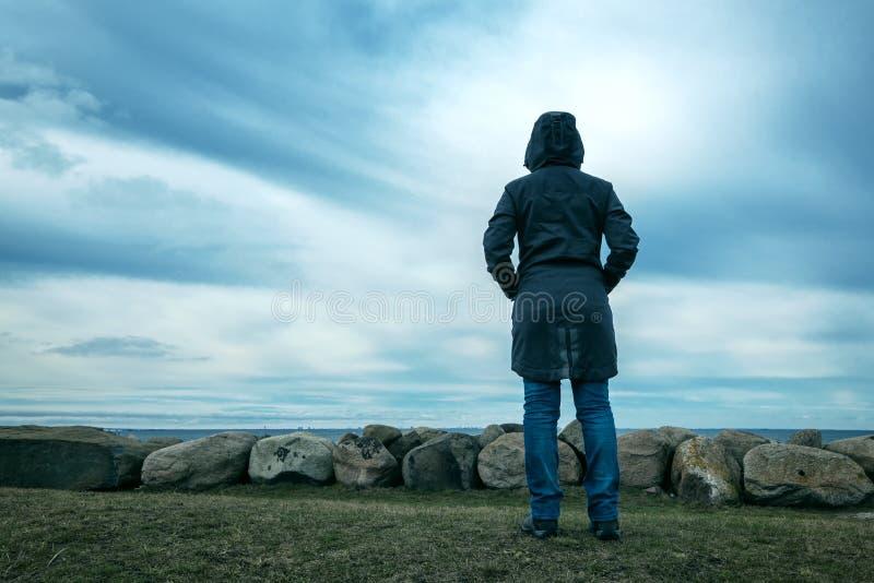 Persona femminile incappucciata sola da dietro la condizione alla spiaggia fotografie stock