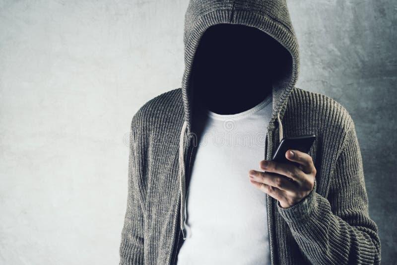 Persona incappucciata anonima che per mezzo del telefono cellulare, concep di furto di identità fotografia stock