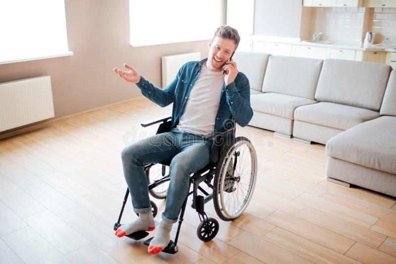 Persona joven con la inclusi?n y la incapacidad El sentarse en la silla de ruedas y el hablar en el tel?fono Hombre joven ocupado foto de archivo
