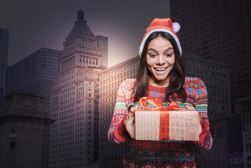 Persona joven emocional que parece excitada mientras que consigue un presente fotos de archivo libres de regalías