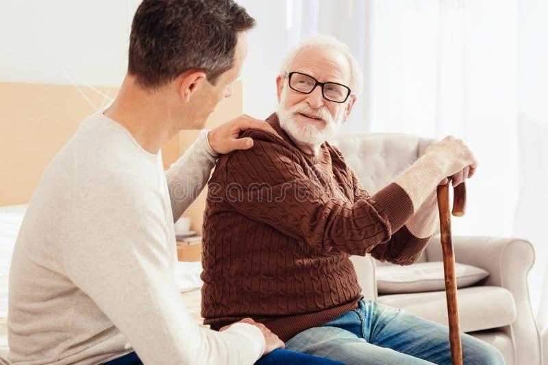 Persona masculina encantada que escucha su pariente imagen de archivo