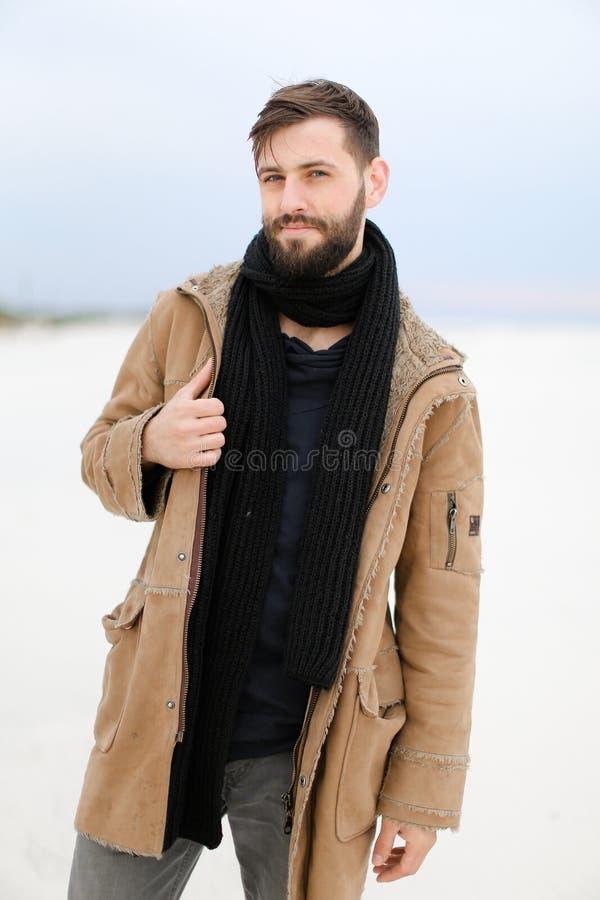 Persona masculina joven caucásica con la capa y la bufanda que llevan de la barba que se colocan en el fondo blanco de la nieve imagen de archivo libre de regalías