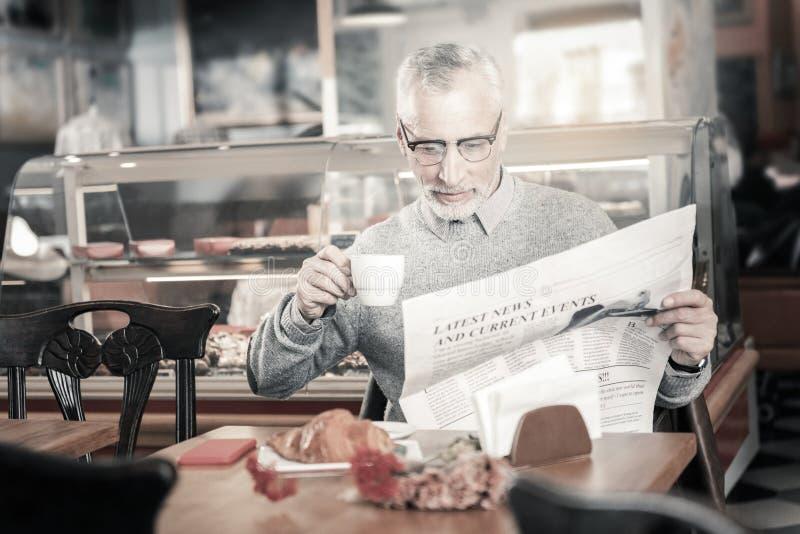 Persona masculina madura contenta que goza del café de la mañana foto de archivo