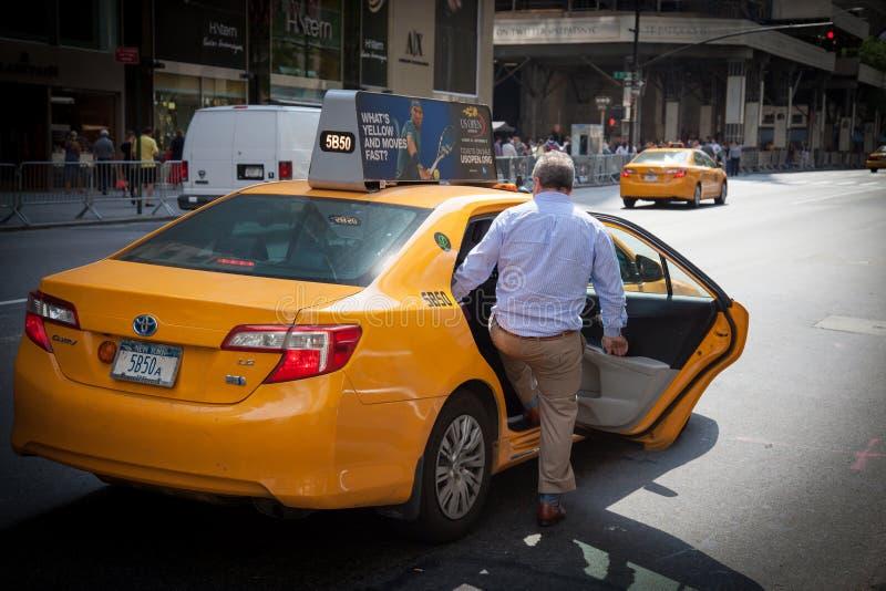 Persona masculina que toma un taxi amarillo foto de archivo libre de regalías