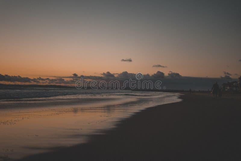 Persona mayor que camina en la playa arenosa hermosa en la puesta del sol imagenes de archivo
