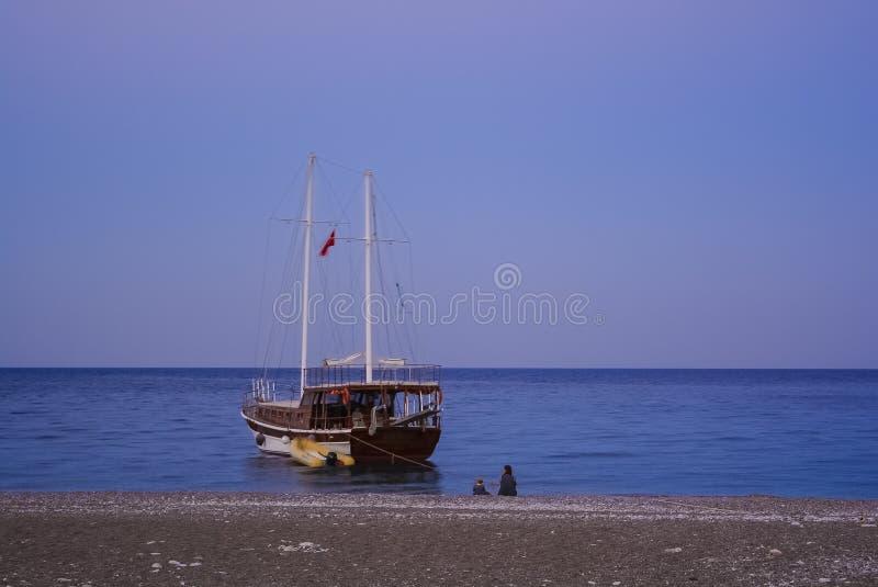 Persona messa mare della barca con la barca a vela del bambino fotografie stock