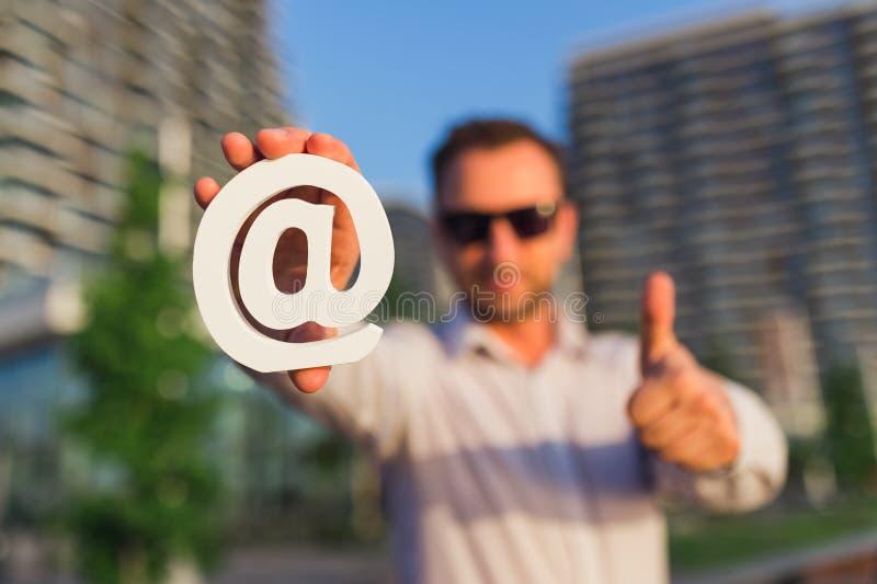 Persona moderna del negocio que muestra los pulgares para arriba y que lleva a cabo símbolo de madera del correo electrónico al a imagen de archivo