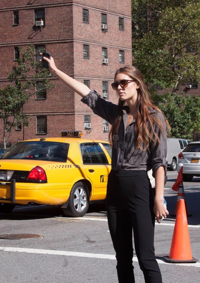Persona mondana che aspetta un taxi a New York immagine stock