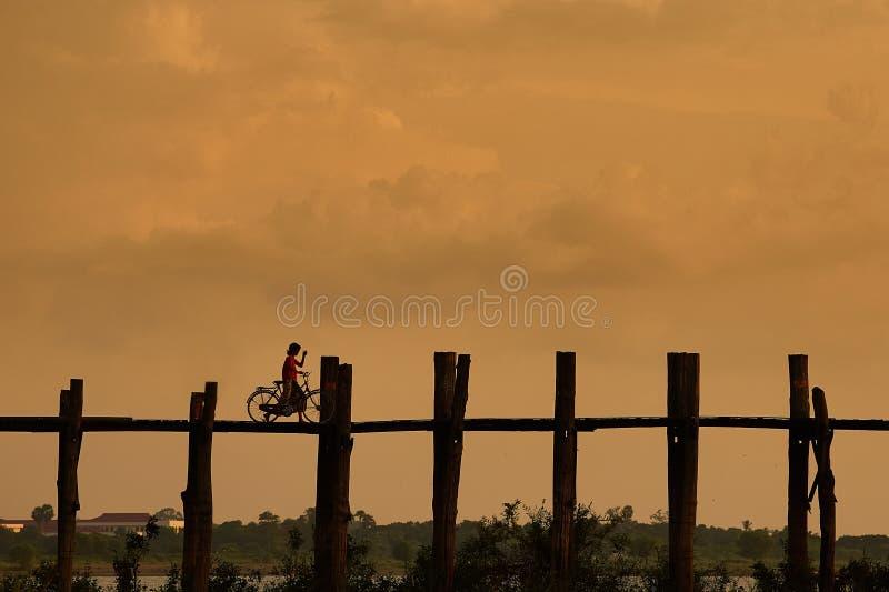 Persona profilata con una bici sul ponte di U Bein fotografie stock libere da diritti
