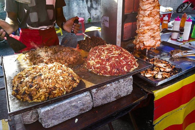 Persona que asa a la parrilla y carne de la asación para la comida del pan Pita del shawarma foto de archivo libre de regalías