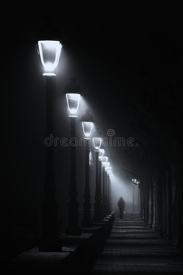 Persona que camina en la calle oscura iluminada con las farolas fotografía de archivo libre de regalías