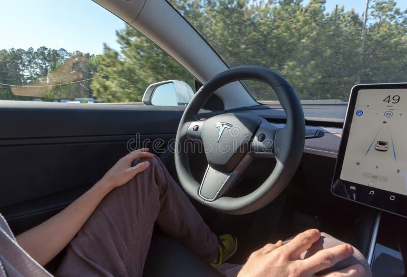 Persona que conduce un nuevo modelo 3 de Tesla en modo del piloto automático foto de archivo libre de regalías