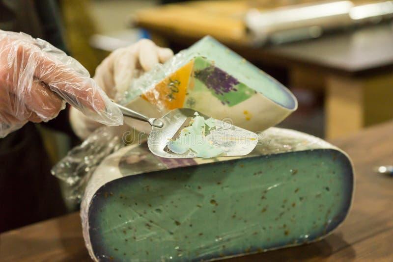 Persona que corta el queso verde con una cortadora imagen de archivo