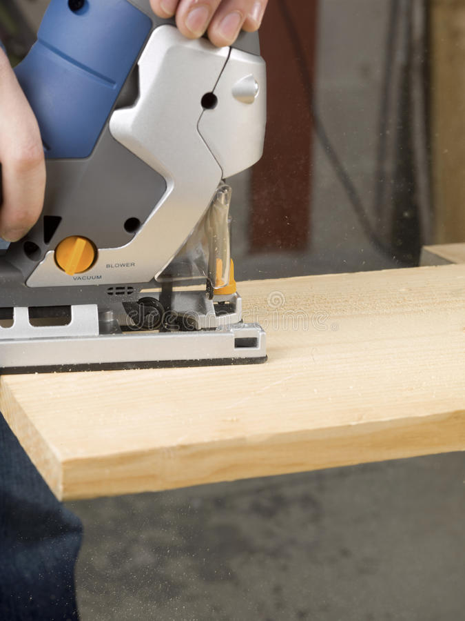 Persona que corta el tablón de madera imagen de archivo