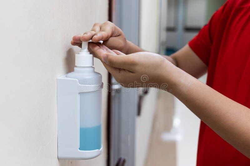 Persona que dispensa el líquido desinfectante del desinfectante sobre la mano en hos imagenes de archivo