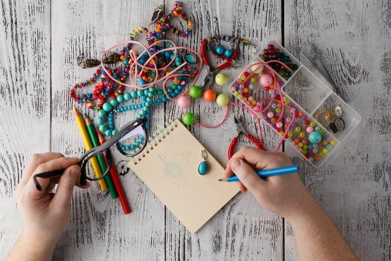 Persona que hace earings de gotas y de agujas coloridas fotos de archivo