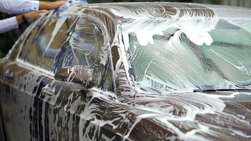 Persona que lava el automóvil costoso con la esponja del jabón, negocio del carwash de la élite foto de archivo libre de regalías