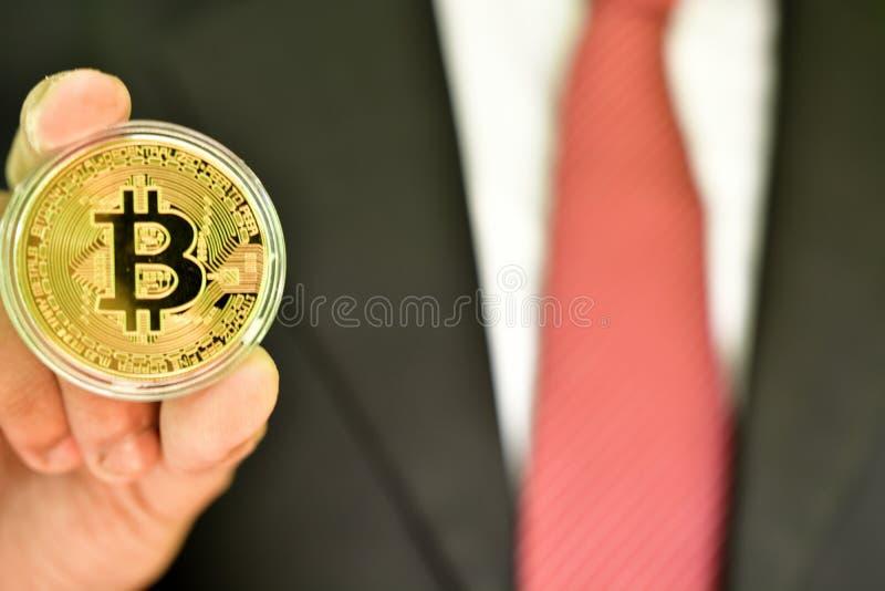 Persona que lleva a cabo el bitcoin de oro del color fotografía de archivo libre de regalías