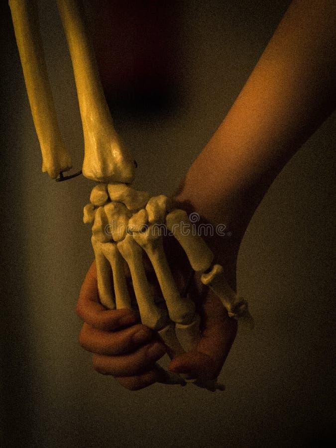 Persona que lleva a cabo las manos con el esqueleto imagen de archivo libre de regalías