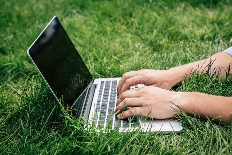 Persona que mecanografía en el ordenador portátil con la pantalla en blanco al aire libre fotos de archivo libres de regalías