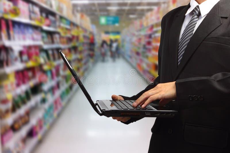 Persona que mecanografía en el ordenador portátil en supermercado en borroso fotografía de archivo