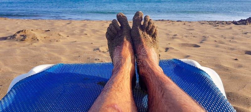 Persona que miente en ocioso azul con sus piernas se?aladas al azul con el mar y a la arena en una playa en Lanzarote, islas Cana imagen de archivo