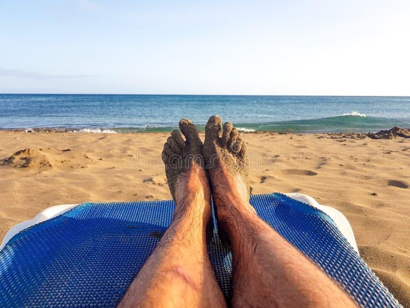 Persona que miente en ocioso azul con sus piernas se?aladas al azul con el mar y a la arena en una playa en Lanzarote, islas Cana fotos de archivo libres de regalías