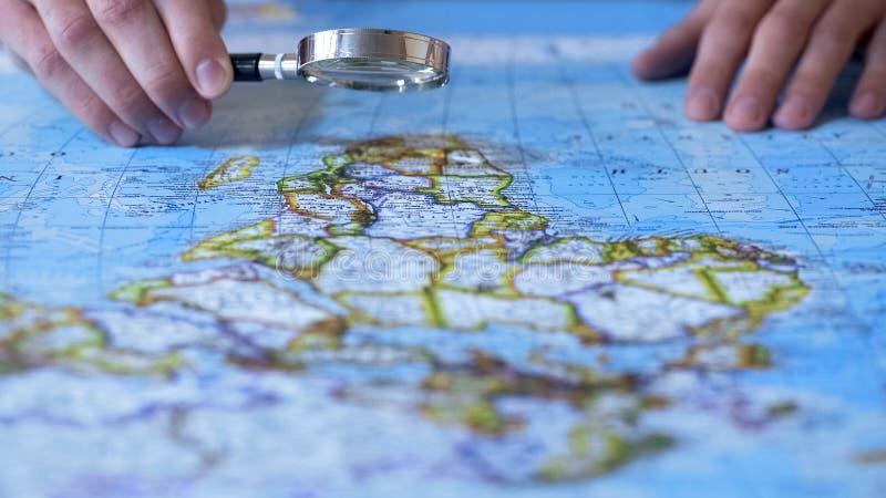 Persona que mira África en mapa a través de la lupa, destino del viaje imagen de archivo