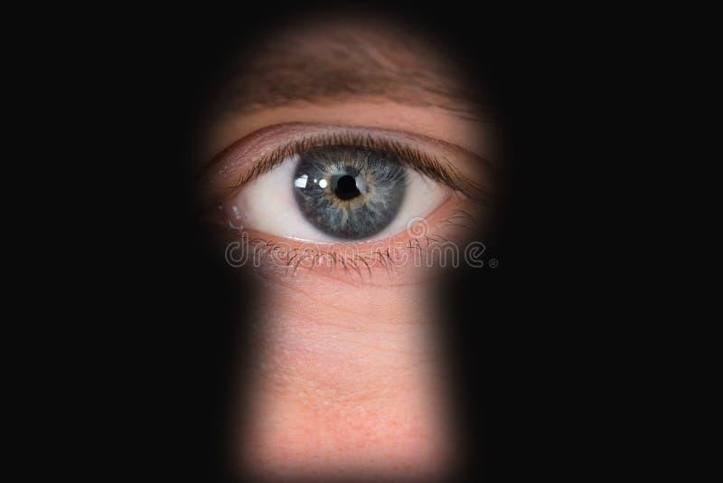 Persona que mira a través del ojo de la cerradura fotos de archivo
