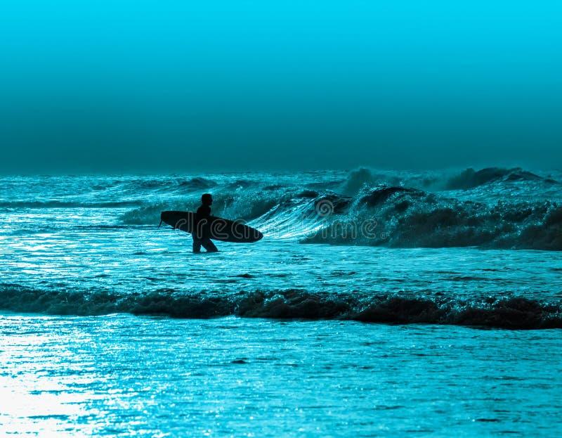 Persona que practica surf atlética con el tablero fotografía de archivo