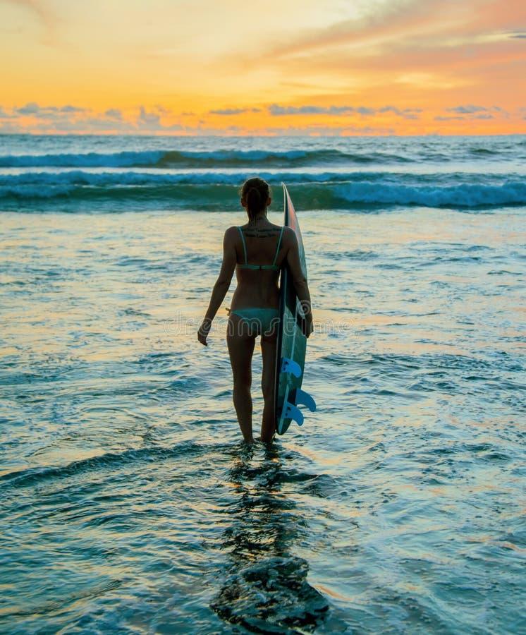 Persona que practica surf con el tablero fotos de archivo