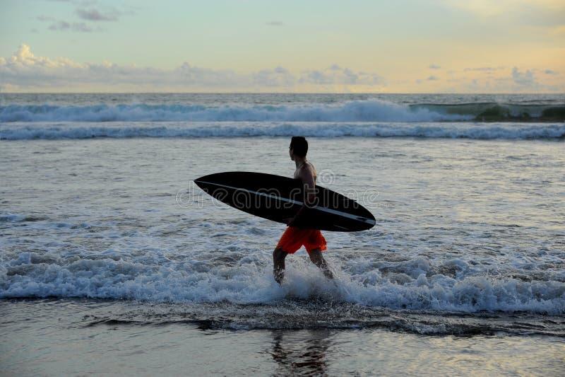 Persona que practica surf con el tablero fotografía de archivo