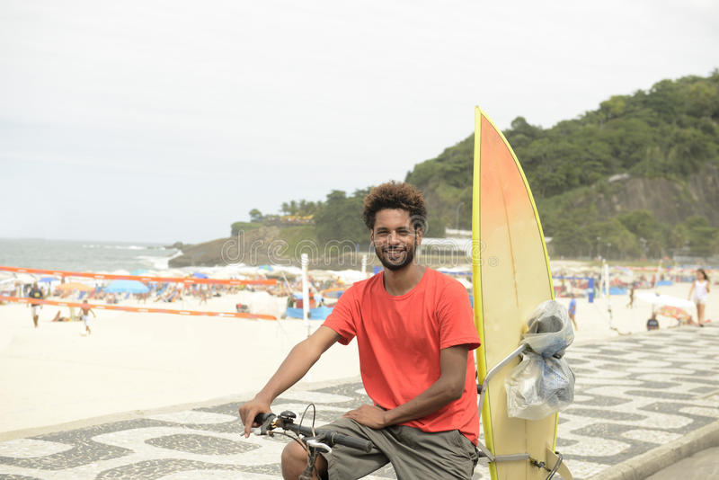 Persona que practica surf con el tablero y la bici imagenes de archivo