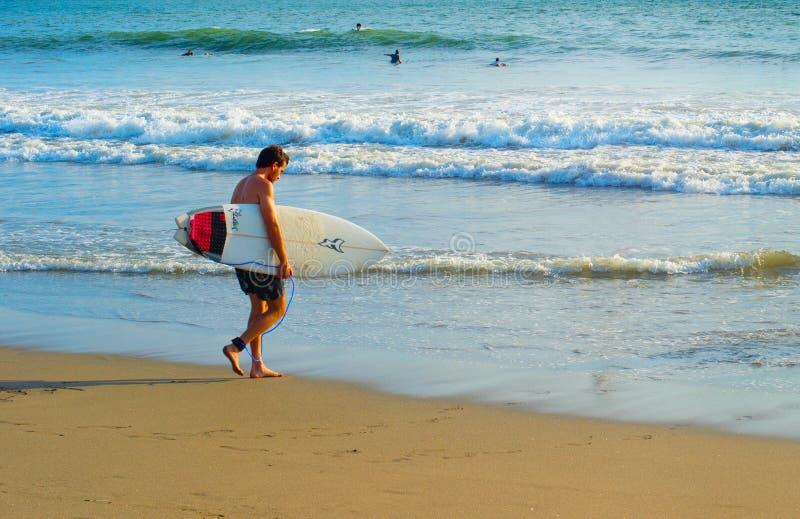 Persona que practica surf con la tabla hawaiana en la playa fotografía de archivo libre de regalías