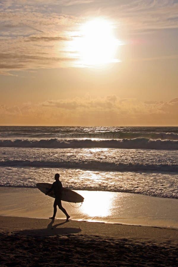 Persona que practica surf con la tarjeta de resaca en la playa, bahía de Fistral, Reino Unido foto de archivo libre de regalías