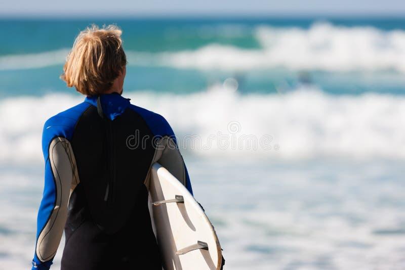 Persona que practica surf con la tarjeta en la playa imagen de archivo