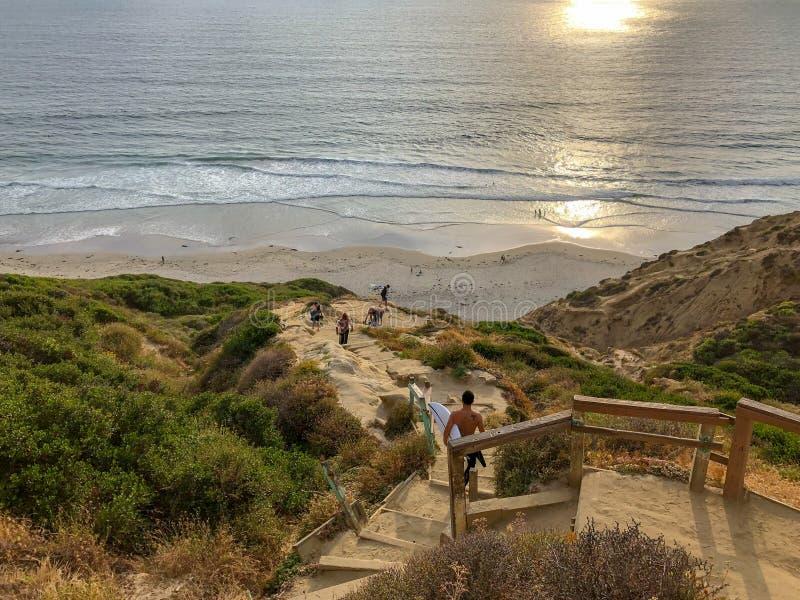 Persona que practica surf con su tablero de resaca que va abajo del acantilado a la playa durante puesta del sol imagenes de archivo